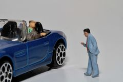 Asking some travel indications from the car. Miniature figurine of a man driving his car and asking some indications about his trip to a citizen royalty free stock photos