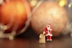 Miniature figurine of Santa Claus with gifts bag royalty free stock photo