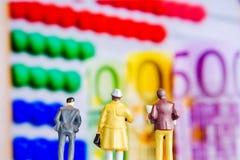 Miniature figurine starring at big defocused euro banknotes stock images