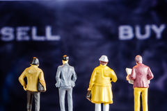 Miniature figurine starring at big defocused sell and buy words. Closeup of miniature figurines of businessmen standing in front of big defocused screen with Stock Photos