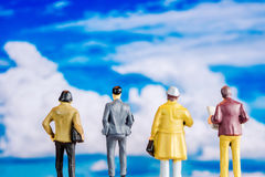 Miniature figurine starring at blue sky with big white clouds Royalty Free Stock Photography