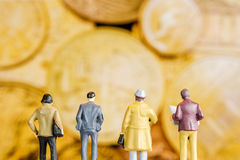 Miniature figurine starring at defocused golden coins. Closeup of miniature figurines of businessmen standing in front of big defocused screen with golden coins Royalty Free Stock Photography