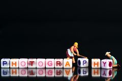 Miniature figurine woman fixing adjusting a Group Of Letters forming Words Spelling. `Photography` on a black glass surface with mirror image stock image