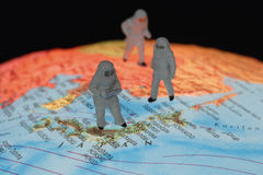 Miniature figurines of astronomers on globe Stock Photo