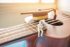 Miniature figurines Businessman sitting on ukulele with Graduati. On cap. Ukuleles is member lute family instruments with nylon stringed, played with bare thumb Royalty Free Stock Photography
