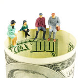 Miniature figurines discussion on the edge of 100 dollar banknot Royalty Free Stock Image