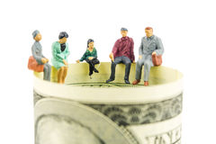 Miniature figurines discussion on the edge of 100 dollar banknote. Miniature figurines sitting on the edge of 100 dollar banknote on white background Royalty Free Stock Photography