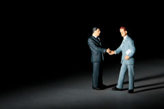 Miniature figurines of handshaking businessmen Stock Image