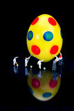 Miniature figurines painting yellow easter egg on black royalty free stock photography