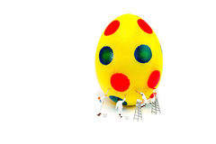 Miniature figurines painting yellow easter egg Royalty Free Stock Photography