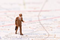 Miniature figurines of  traveller with map background. Business concept Royalty Free Stock Photography