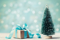 Miniature fir tree and christmas gift box against blue bokeh background. Holiday greeting card. Stock Images