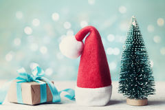 Miniature fir tree, santa hat and christmas gift box against blue bokeh background. Holiday greeting card. Stock Images