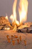 Miniature firemen at a car accident scene in flames Stock Images