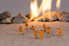 Miniature firemen at work near real fire Stock Images