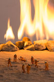 Miniature firemen at work near real fire Stock Photography