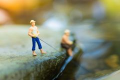 Miniature fisherman sitting on stone, fishing in the river. Macro view photo, use as a fishing career concept.  Royalty Free Stock Photo