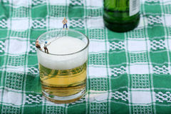 Miniature fishermen. Fishing on the edge of a glass full of beer Stock Images