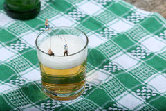 Miniature fishermen. Fishing on the edge of a glass full of beer Royalty Free Stock Image