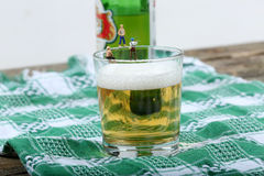 Miniature fishermen. Fishing on the edge of a glass full of beer Stock Image