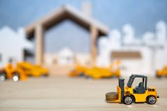 Miniature forklift model lifting gold coins stock photography