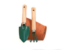 Miniature gardening tools. Miniature gardening tools used for window box and table top gardening rersting against a terracotta flower pot and on a white Royalty Free Stock Photos