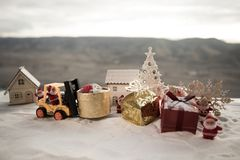 Miniature Gift Box by Forklift Machine on snow ,Determined Image for Christmas Holiday and Happy New Year Gift Celebration concept. Selective focus stock photography