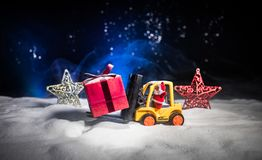 Miniature Gift Box by Forklift Machine on snow ,Determined Image for Christmas Holiday and Happy New Year Gift Celebration concept. Selective focus stock image