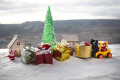 Miniature Gift Box by Forklift Machine on snow ,Determined Image for Christmas Holiday and Happy New Year Gift Celebration concept. Selective focus royalty free stock image