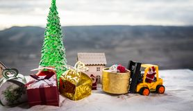 Miniature Gift Box by Forklift Machine on snow ,Determined Image for Christmas Holiday and Happy New Year Gift Celebration concept. Selective focus stock photo