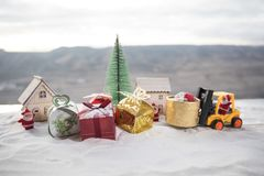 Miniature Gift Box by Forklift Machine on snow ,Determined Image for Christmas Holiday and Happy New Year Gift Celebration concept. Selective focus stock photos