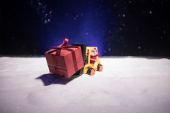 Miniature Gift Box by Forklift Machine on snow ,Determined Image for Christmas Holiday and Happy New Year Gift Celebration concept royalty free stock photos
