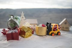 Miniature Gift Box by Forklift Machine on snow ,Determined Image for Christmas Holiday and Happy New Year Gift Celebration concept stock photography