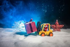 Miniature Gift Box by Forklift Machine on snow ,Determined Image for Christmas Holiday and Happy New Year Gift Celebration concept. Selective focus royalty free stock photo