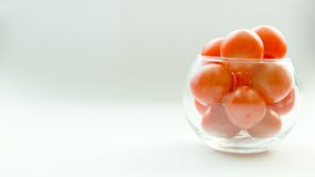 Miniature glass jar full of small tomatoes Royalty Free Stock Photos