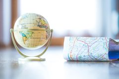 Miniature globe model on a rustic wooden table. Symbol for travelling. Planning the next journey: miniature globe on a rustic table travel earth transport world royalty free stock photo