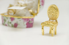 Miniature golden chair. Wedding favor with jewel box and shallow dof Royalty Free Stock Photo