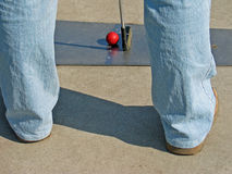 Miniature golf. Man playing mini golf outdoor with club and red ball Stock Photos