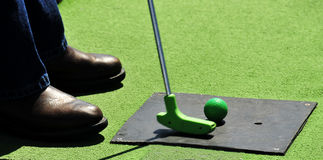 Miniature golf. Golfer getting ready to putt on a miniature golf course royalty free stock photography