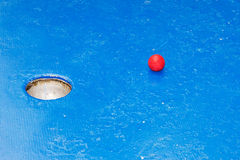 Miniature golf. Hole of a blue miniature golf course with a red ball Stock Photo