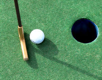 Miniature Golf. A putter and a white golf ball lined up with the hole on green Stock Photo