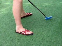Miniature Golf. Green with woman's feet and putter Royalty Free Stock Images