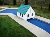 Miniature Golf Church Hole. A little white church which is an obstacle on the miniature golf course. Flowers in the background Stock Image