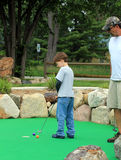 Miniature Golf Family. A young boy and his grandfather are playing miniature golf.  The boy is hitting his ball into the hole as the grandfather watches on Stock Photography