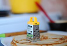 Miniature grater on a stack of pancakes. Miniature yellow grater on a stack of pancakes Royalty Free Stock Photography