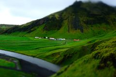 Miniature green farmland near mountain and river. On Iceland. Magical place Royalty Free Stock Photos
