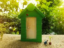 Miniature Greenhouse concept, alone of miniature mini figures wi. Th planting tree in front of the green house. protect nature and environment concept Royalty Free Stock Image