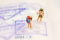 Miniature Group traveler with backpack standing on passport with copy space for travel around the world. Travel Concept Royalty Free Stock Photography