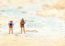 Miniature Group traveler with backpack standing on wold map for travel around the world. royalty free stock image