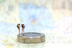 Miniature Group traveler with backpack standing on wold map for travel around the world. royalty free stock photos
